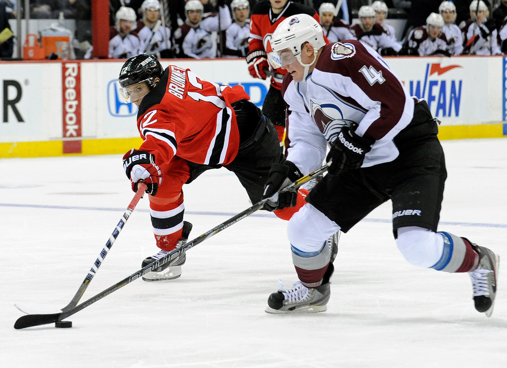 . New Jersey Devils\' Damien Brunnner, left, attempts to knock the puck away from Colorado Avalanche\'s Tyson Barrie during the second period of an NHL hockey game Monday, Feb. 3, 2014, in Newark, N.J. (AP Photo/Bill Kostroun)