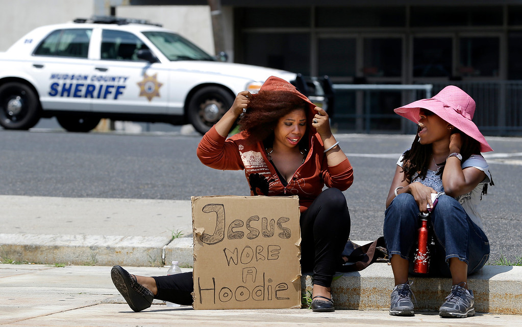 """. Mya Chavis, left, adjusts a the hood of  a jacket over herself while sitting with Danyse Ryan while they wait for a rally to start outside of William T. Brennan Courthouse, Saturday, July 20, 2013, in Jersey City, N.J. The Rev. Al Sharpton\'s National Action Network organized \""""Justice for Trayvon\"""" rallies nationwide to press for federal civil rights charges against George Zimmerman, who was found not guilty in the shooting death of unarmed teenager Trayvon Martin. (AP Photo/Julio Cortez)"""