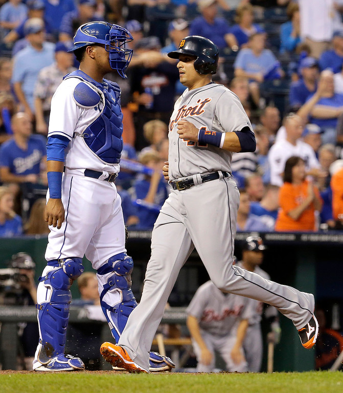. Detroit Tigers\' Victor Martinez runs home past Kansas City Royals catcher Salvador Perez to score on a single by Eugenio Suarez during the first inning of a baseball game Friday, Sept. 19, 2014, in Kansas City, Mo. (AP Photo/Charlie Riedel)
