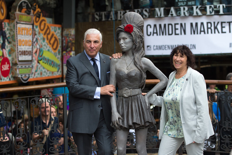 . Mitch Winehouse and Janis Winehouse pose for a picture with a statue of their late daughter, Amy Winehouse after it was unveiled in Camden\'s Stables Market, in London, England, Sunday, Sept. 14, 2014. Three years after her death the unveiling coincides with what would have been her 31st birthday. (AP Photo/Tim Ireland)
