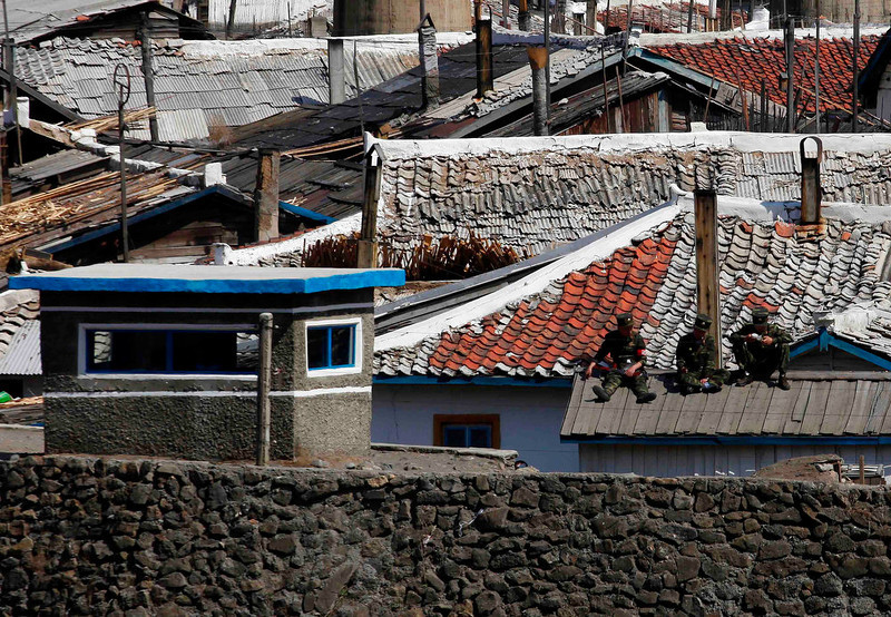 . Men sit on a roof near the North Korean city of Hyesan, across the Yalu River from the Chinese town of Changbai May 12, 2013. Chinese currency and U.S. dollars are being used more widely than ever in North Korea instead of the country\'s own money. The use of dollars and Chinese yuan, or renminbi, has accelerated since a revaluation of the North Korean won in 2009 wiped out the savings of millions of people, said experts on the country, defectors and Chinese border traders.  REUTERS/John Ruwitch