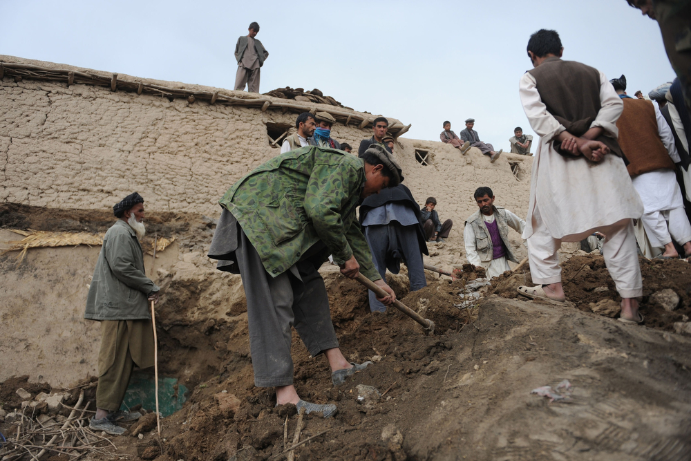. Afghan rescuers search for survivors trapped under the mud in Argo district of Badakhshan province on May 3, 2014 after a massive landslide May 2 buried a village. Rescuers searched in vain for survivors May 3 after a landslide buried an Afghan village, killing 350 people and leaving thousands of others feared dead amid warnings that more earth could sweep down the hillside. Local people made desperate efforts to find victims trapped under a massive river of mud that engulfed Aab Bareek village in Badakhshan province, where little sign remained of hundreds of destroyed homes. (FARSHAD USYAN/AFP/Getty Images)