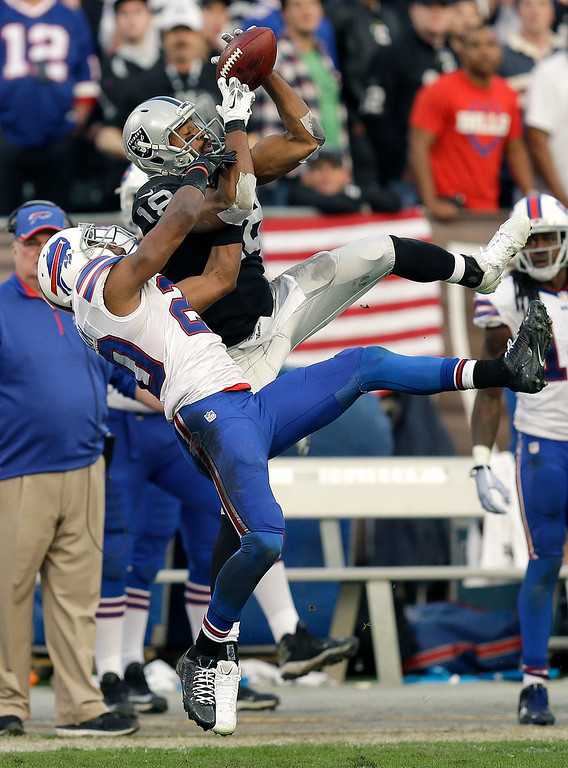 . Oakland Raiders wide receiver Andre Holmes (18) catches a pass over Buffalo Bills cornerback Corey Graham (20) during the fourth quarter of an NFL football game in Oakland, Calif., Sunday, Dec. 21, 2014. (AP Photo/Ben Margot)