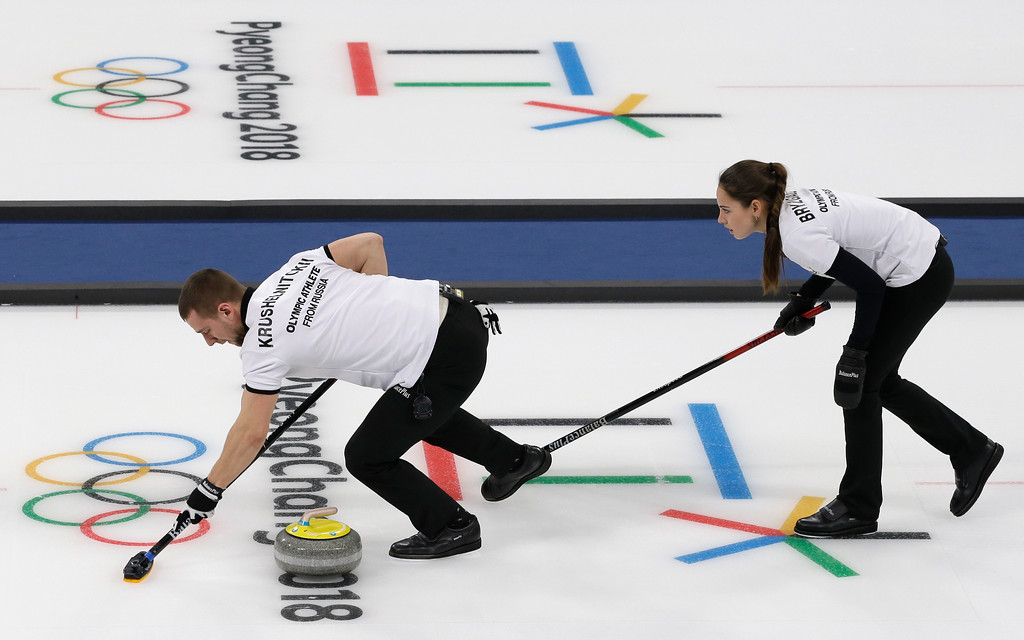 . Olympic Athletes from Russia Aleksandr Krushelnitckii , left, and Anastasia Bryzgalova sweep ice during their mixed doubles curling match again at the 2018 Winter Olympics in Gangneung, South Korea, Sunday, Feb. 11, 2018. (AP Photo/Aaron Favila)