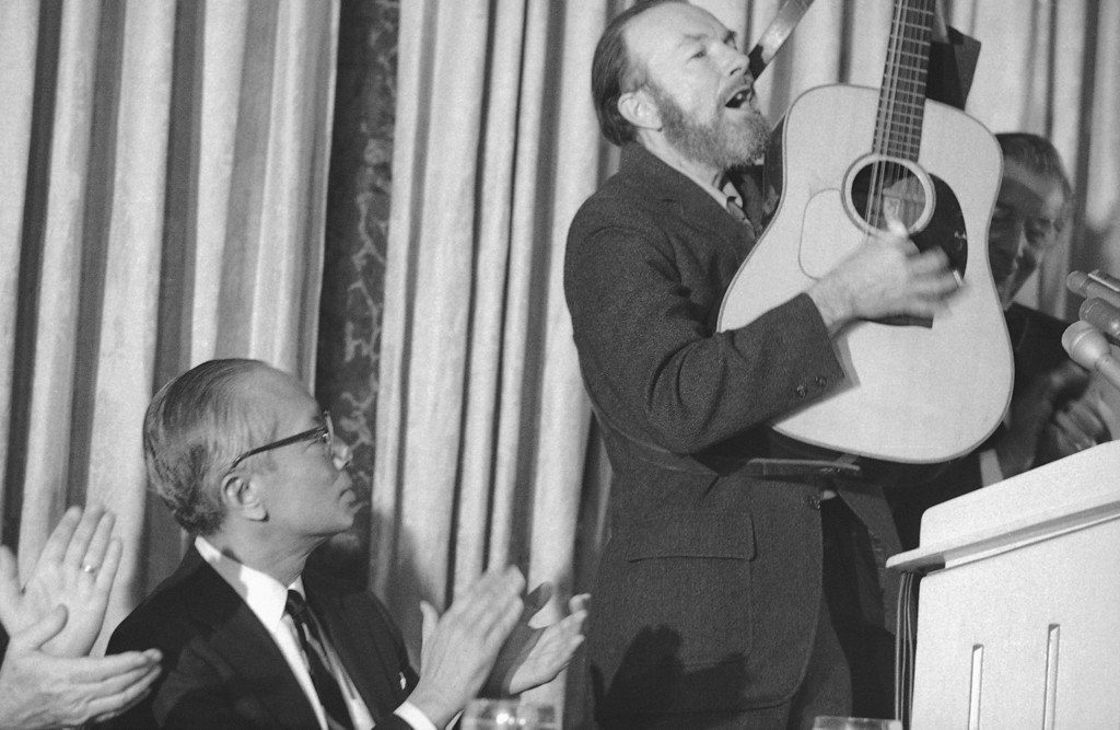 . Retiring U.N. Secretary General U. Thant, left, is shown listening to a song by folk singer Pete Seeger at luncheon honoring Thant at the hotel Pierre in New York on Dec. 14, 1971. (AP Photo/Marty Lederhandler)