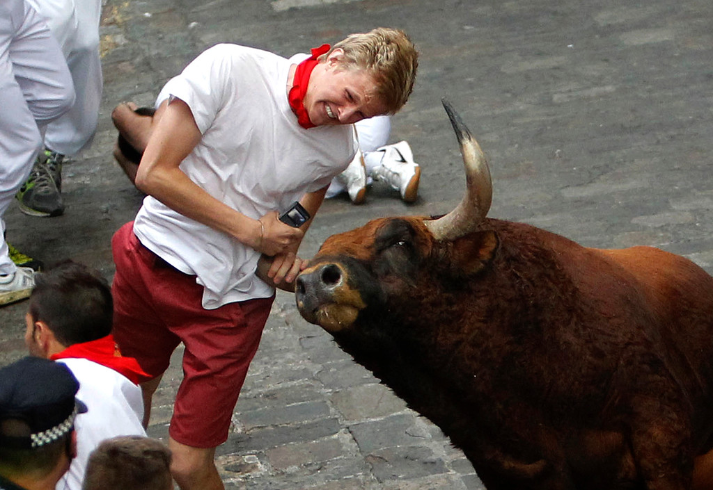 ". A runner is gored by an ""El Pilar\"" fighting bull during the running of the bulls at the San Fermin festival, in Pamplona, Spain, Friday, July 12, 2013. An American and two Spaniards were gored Friday during a danger-filled sixth bull run of Spainís San Fermin festival, with one loose bull causing panic in the packed streets of Pamplona city.  (AP Photo)"