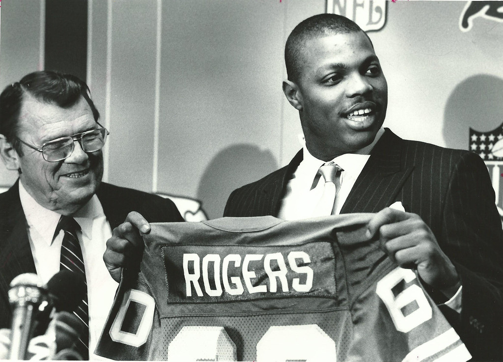 . Former Lions player Reggie Rogers, drafted No. 7 overall by Detroit in the 1987 NFL Draft, shows off his new No. 60 jersey with then-Lions general manager Russ Thomas (left). Oakland Press file photo