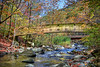 Long wooden bridge crossing over a mountain stream during fall.