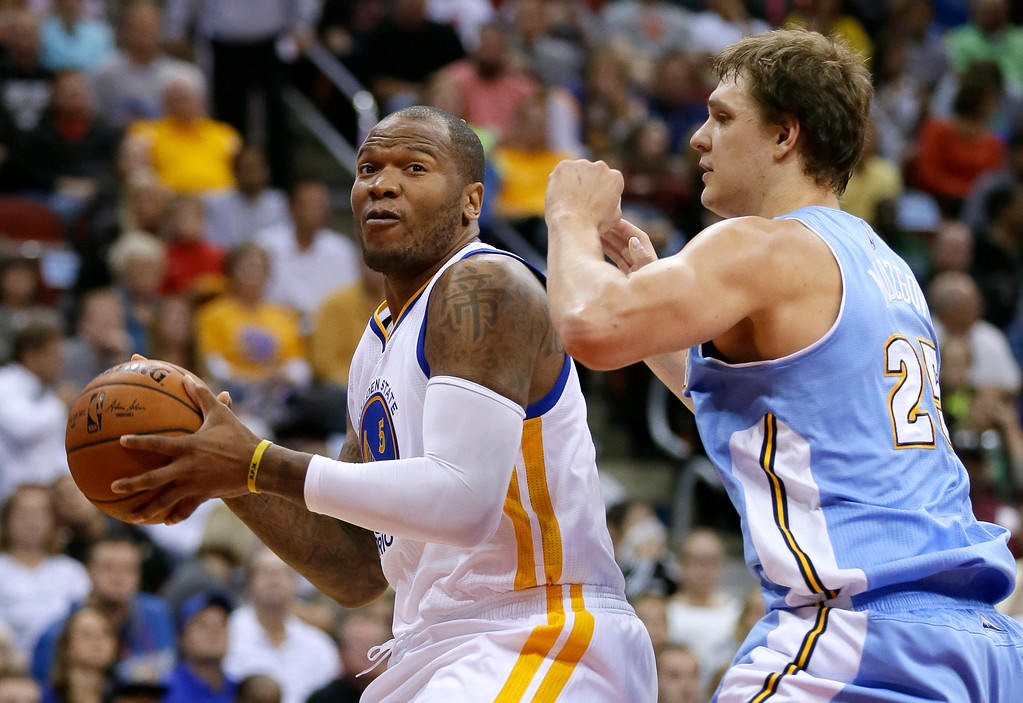 . Golden State Warriors forward Marreese Speights, left, looks to drive around Denver Nuggets center Timofey Mozgov during the first half of a preseason NBA basketball game, Thursday, Oct. 16, 2014, in Des Moines, Iowa. (AP Photo/Charlie Neibergall)