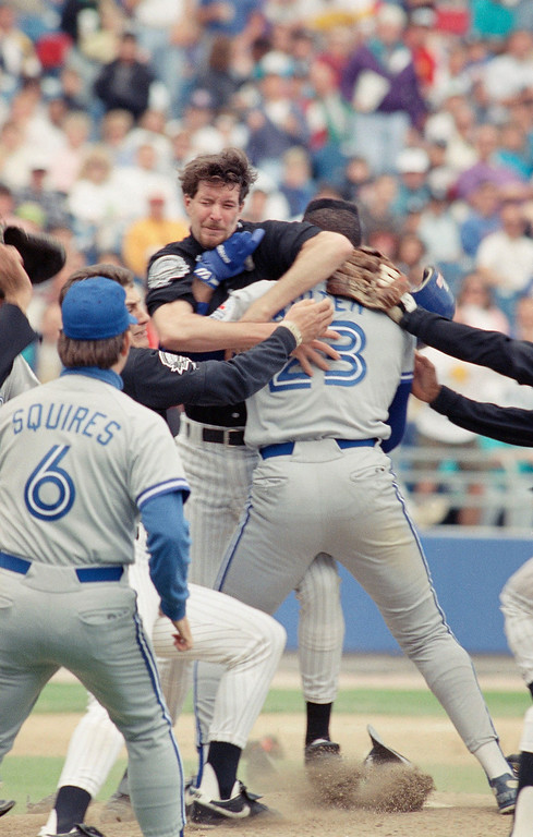 . Toronto Blue Jays Mark Whiten (23) grabs Chicago White Sox pitcher Jack McDowell after charging the mound following a pitch thrown behind his back, May 20, 1991, Chicago, Ill. The brawl cleared the benches and both McDowell and Whiten were ejected following he incident. At left is Blue Jays coach Mike Squires. The White Sox beat the Blue Jays 5-4. (AP Photo/Jonathan Kirn)
