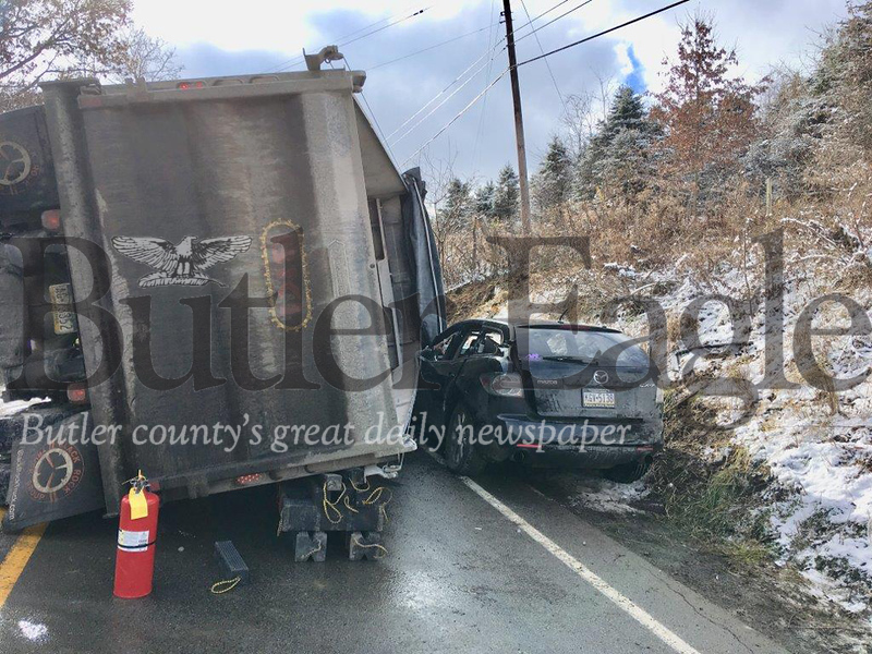 An overturned dump truck rests partially on a sport utility vehicle following a collision about 10 a.m. Friday on Route 308 in Center Township. 3 Column Photo.