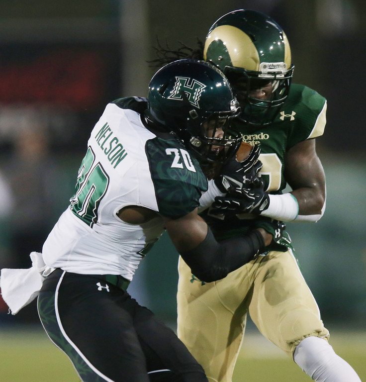 . Hawaii defensive back Nick Nelson, left, tackles Colorado State running back Dee Hart after a long gain early in the first quarter of an NCAA college football game in Fort Collins, Colo., on Saturday, Nov. 8, 2014. (AP Photo/David Zalubowski)