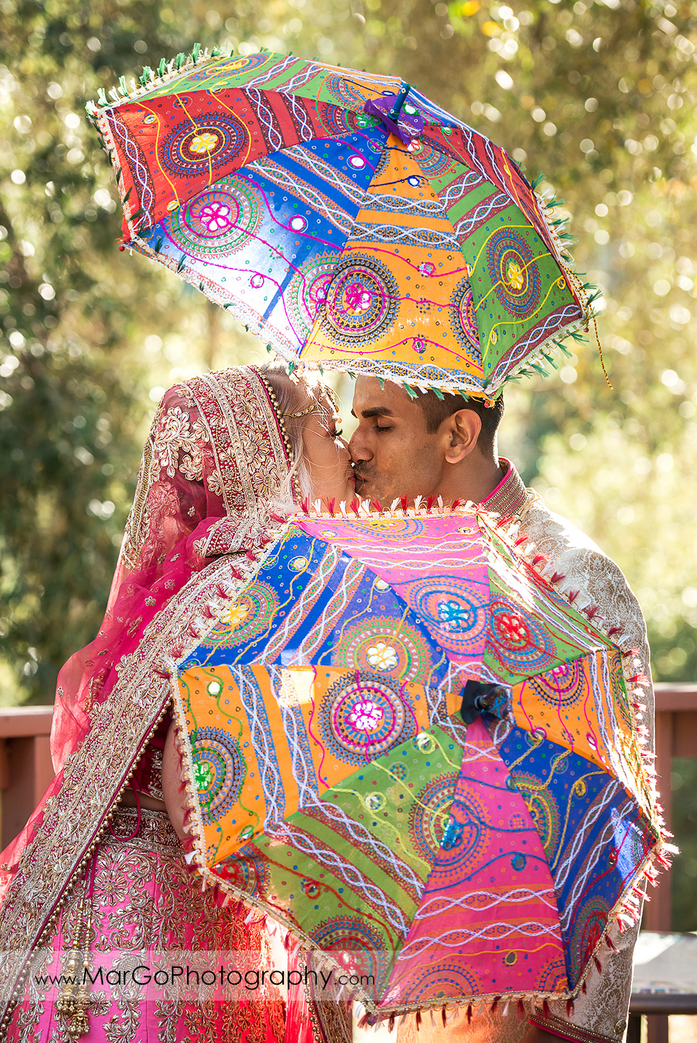 Indian bride and groom in golden and pink outfits kissing behind colorful umbrellas at Elliston Vineyards in Sunol