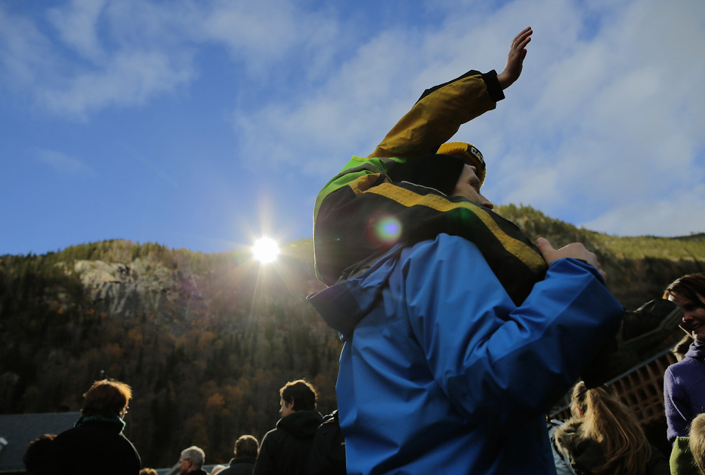 . Sunlight is reflected by huge mirrors as a man carries a child in Rjukan, Norway on October 30, 2013 during the opening event of a project to reflect sunlight in the steep-sided valley. A computer will control mirrors so that they follow the sun to reflect the light on the market square that is deprived from direct sunlight six months a year, from September to March. AFP PHOTO / SOERBOE Krister/AFP/Getty Images