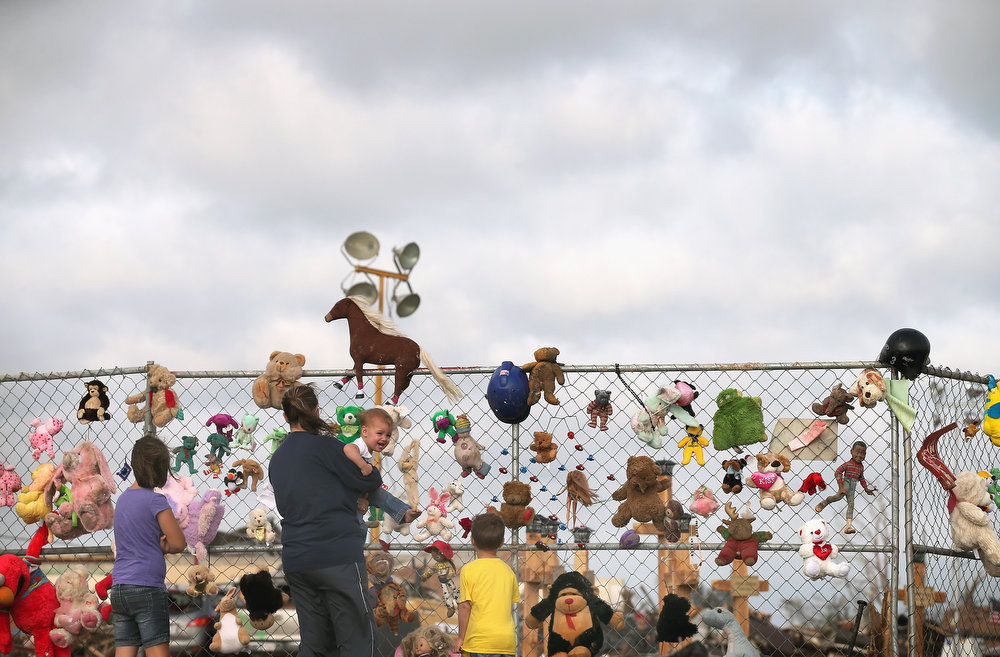 . A family visits a memorial attached to a fence outside the Plaza Towers Elementary School on May 27, 2013 in Moore, Oklahoma. The school was destroyed and seven children were killed when a tornado struck the school on May 20. Residents and volunteers observed the Memorial Day holiday by continuing to recover valuables from the destroyed neighborhoods. The tornado of EF5 strength and two miles wide touched down May 20 killing at least 24 people and leaving behind extensive damage to homes and businesses. U.S. President Barack Obama promised federal aid to supplement state and local recovery efforts.  (Photo by Scott Olson/Getty Images)