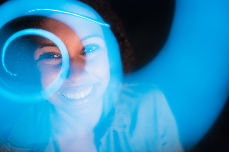 Portrait of a female looking through blue spiral.