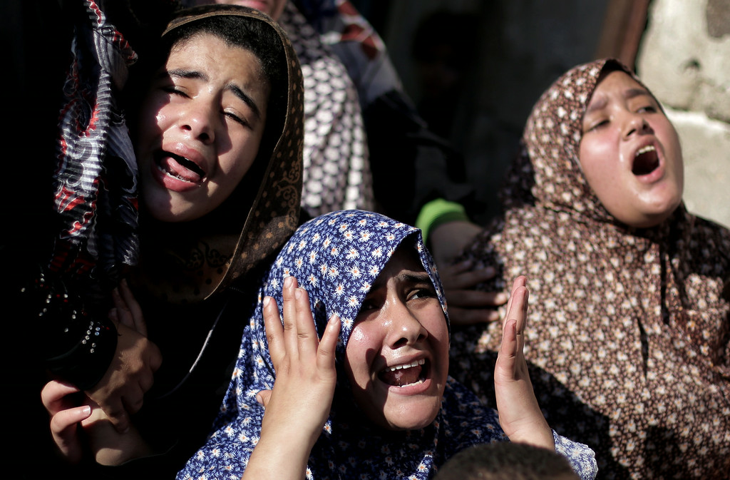 . Palestinian relatives of four boys from the same extended Bakr family, grieve during their funeral in Gaza City, Wednesday, July 16, 2014.  The four boys, who were cousins and ages 9 to 11, were killed while playing on a beach off a coastal road west of Gaza City, said Ashraf Al Kedra, a Palestinian doctor. Seven others _ adults and children _ were wounded in the strike, he said. (AP Photo/Khalil Hamra)
