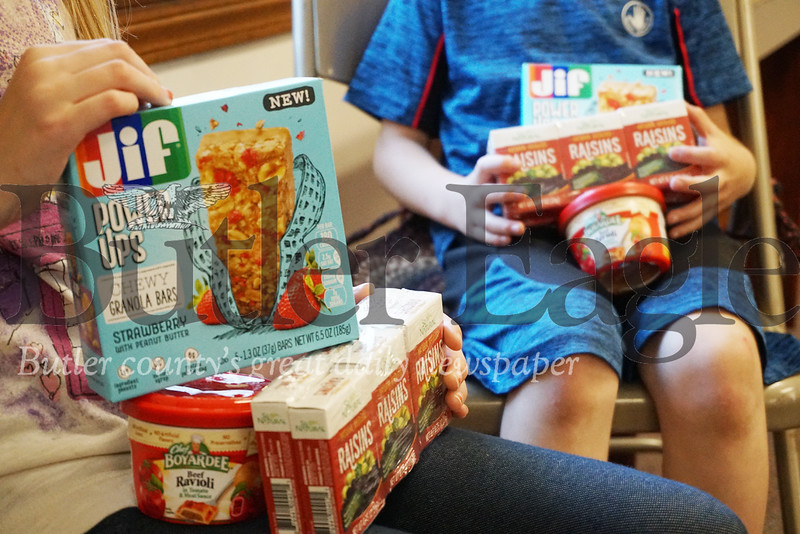 Photo by J.W. Johnson Jr.Children hold some of the items contained in boxes distributed as part of the Southwest Butler Food Cupboard's Kits4Kids Program.
