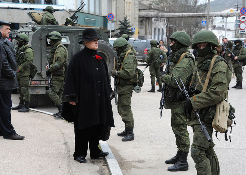 . A woman waits in front of unidentified men in  military fatigues blocking a base of the Ukrainian frontier guard unit in Balaklava on March 1, 2014.  Ukraine\'s border guard service said  that about 300 armed men were attempting to seize its main headquarters in the Crimean port city of Sevastopol under orders from Russian Defence Minister Sergei Shoigu.  (VIKTOR DRACHEV/AFP/Getty Images)