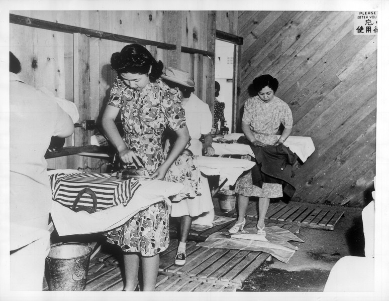 """""""Ironing -- From the washing room the Japanese women proceed to the ironing room which is right next to the washing room at Santa Anita Assembly Center.""""--caption on photograph"""