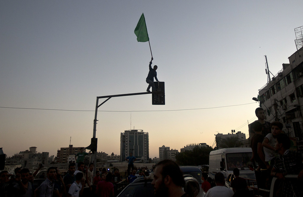 """. A Palestinian plants a Hamas flag atop a street light as people gather in the streets of Gaza City on August 26, 2014, to celebrate the long-term truce agreed between Israel and the Palestinians. Israel has agreed to observe an \""""unlimited\"""" ceasefire in the Gaza Strip, a senior official told AFP on Tuesday, shortly after the deal was announced by the Palestinians. MAHMUD HAMS/AFP/Getty Images"""