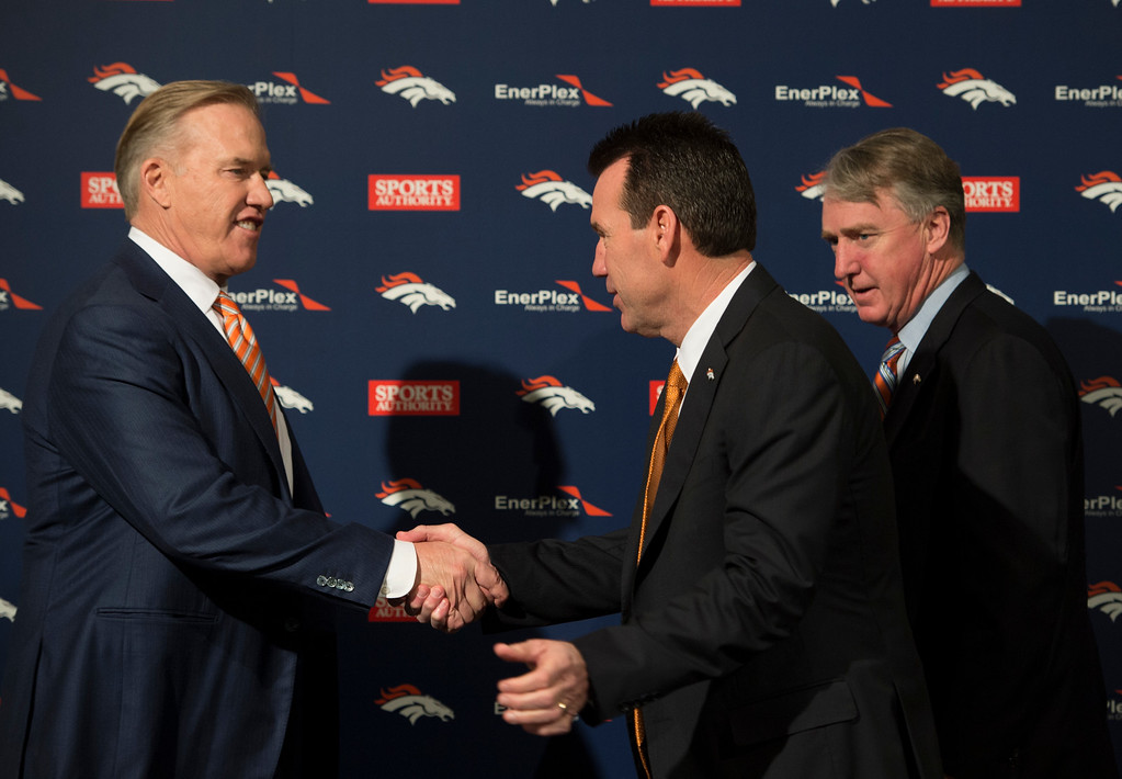 . Denver Broncos John Elway, General Manager and Executive Vice President of Football Operations shakes hands with Head Coach Gary Kubiak as Joe Ellis President and CEO looks on after a press conference January 20, 2015 at Dove Valley. Kubiak becomes the 15th head coach in franchise history. (Photo By John Leyba/The Denver Post)
