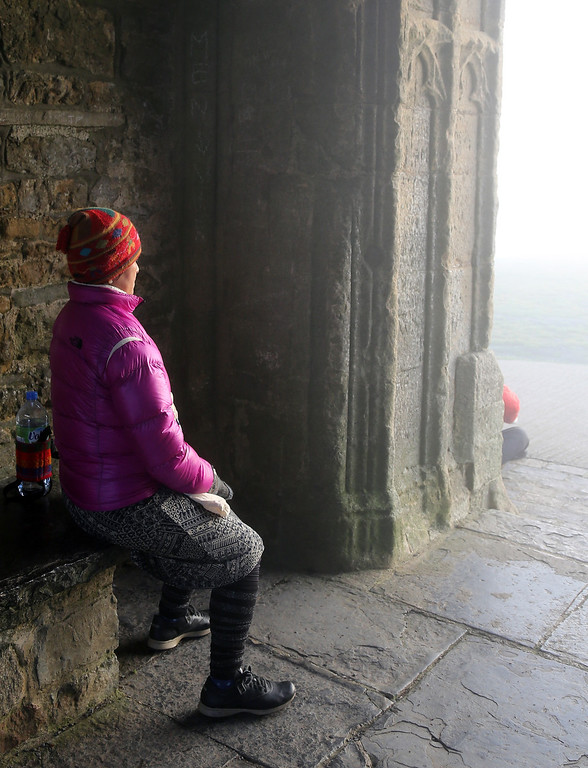 . A visitor to Glastonbury Tor meditates inside St. Michael\'s Tower, a ruined 14th-century church tower, as the rising sun begins to clear the early morning mist and fog near the town of Glastonbury on September 4, 2013 in Somerset, England.   (Photo by Matt Cardy/Getty Images)