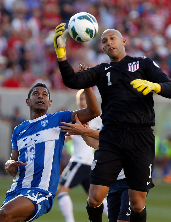 . U.S. goalkeeper Tim Howard (R) makes a save while pressured by Honduras\' Carlo Costly (13) during their 2014 World Cup qualifying soccer match in Salt Lake City, Utah, June 18, 2013. REUTERS/Jim Urquhart