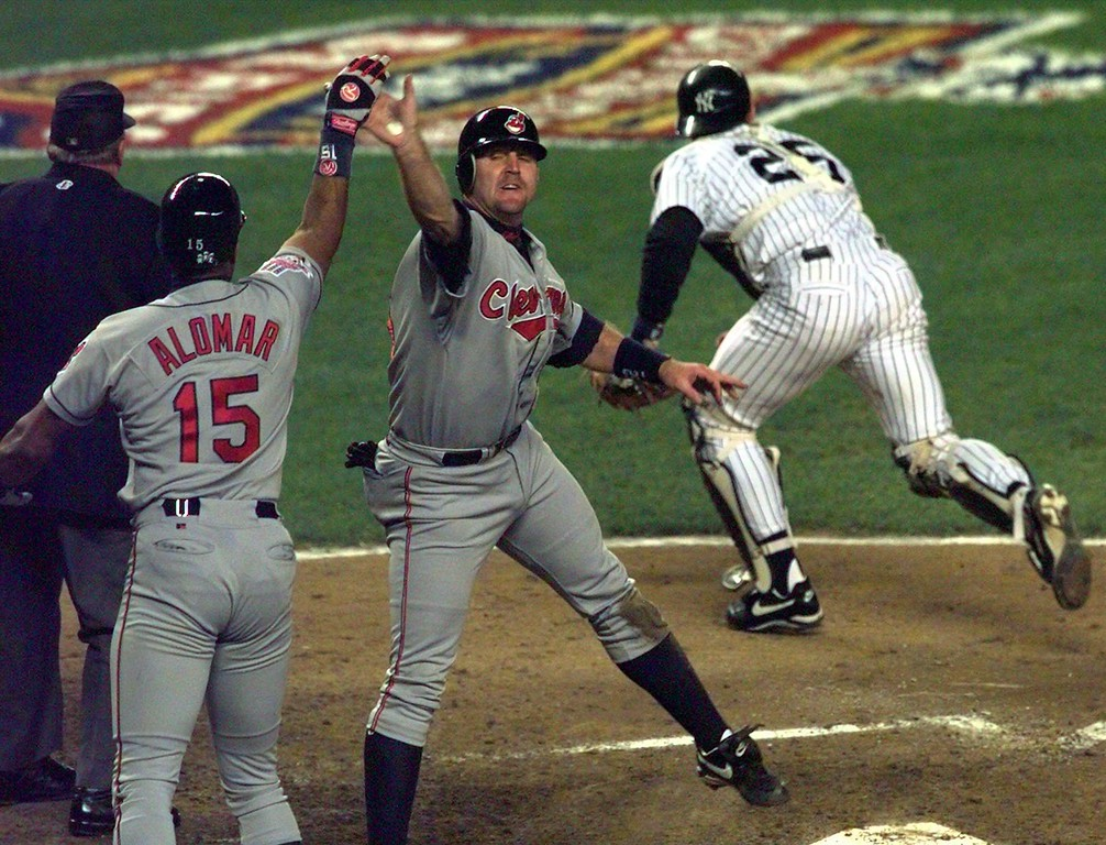 . Cleveland Indians\' Sandy Alomar, left, high fives Jim Thome after they were driven in by teammate Tony Fernandez in the fourth inning against the New York Yankees in Game 2 of their American League Division Series at New York\'s Yankee Stadium on Thursday, Oct. 2, 1997. At right is Yankees catcher Joe Girardi. (AP Photo/ Ron Frehm)