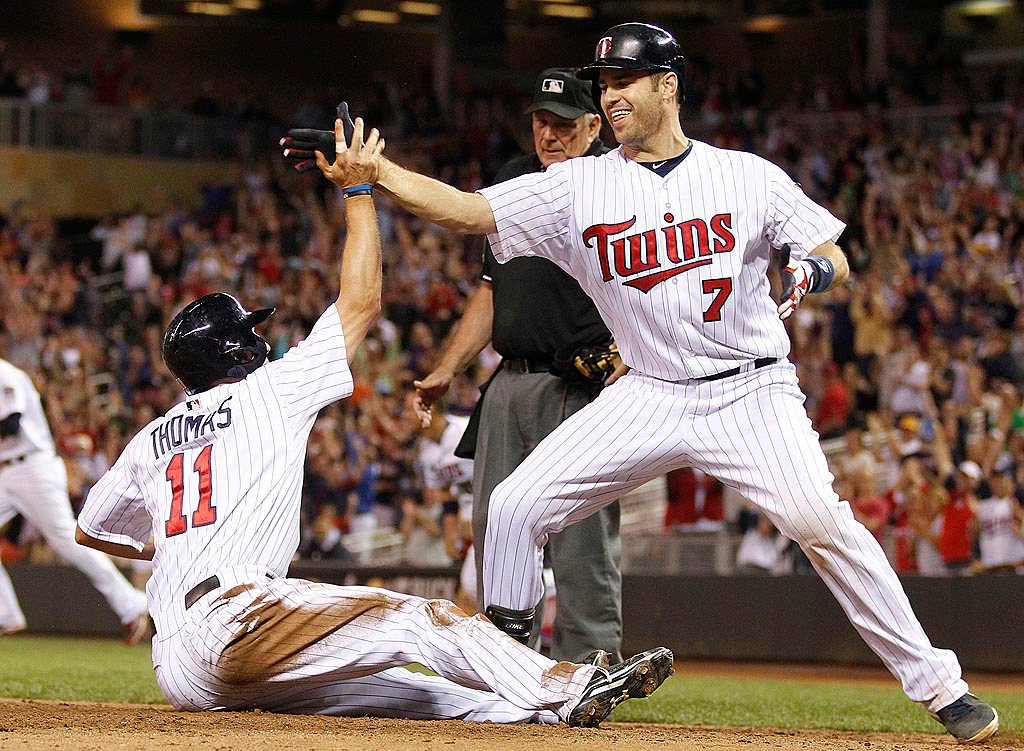 . Minnesota Twins Clete Thomas is congratulated by teammate Joe Mauer after Thomas scored on an RBI single by Brian Dozier in the 13th inning. (AP Photo/Andy Clayton-King)