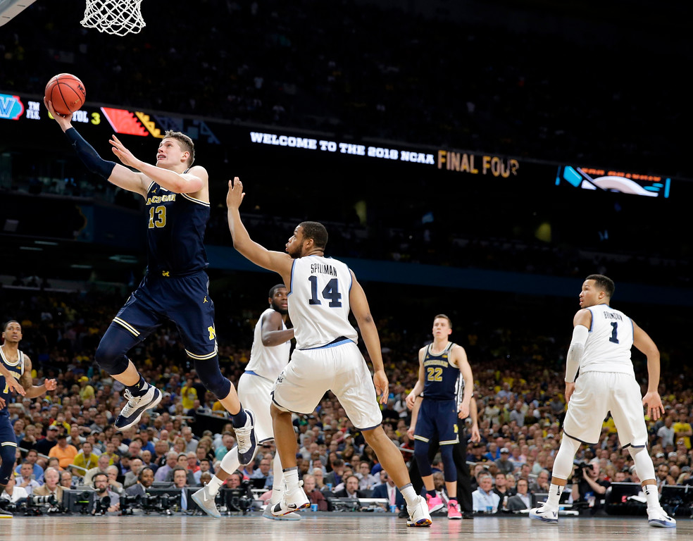 . Michigan\'s Moritz Wagner (13) goes up for a shot past Villanova\'s Omari Spellman (14) during the second half in the championship game of the Final Four NCAA college basketball tournament, Monday, April 2, 2018, in San Antonio. (AP Photo/Eric Gay)