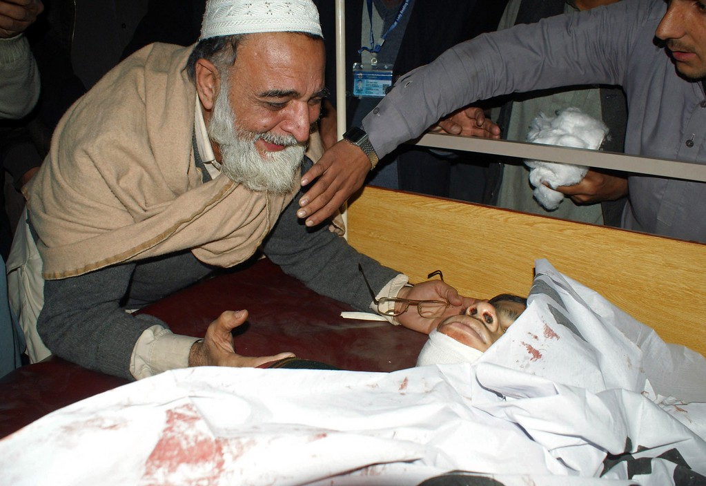 . A Pakistani father mourns beside the body of his son at a hospital following an attack by Taliban gunmen on a school in Peshawar on December 16, 2014. Taliban insurgents killed at least 130 people, most of them children, after storming an army-run school in Pakistan December 16 in one of the country\'s bloodiest attacks in recent years. AFP PHOTO/ A  Majeed/AFP/Getty Images