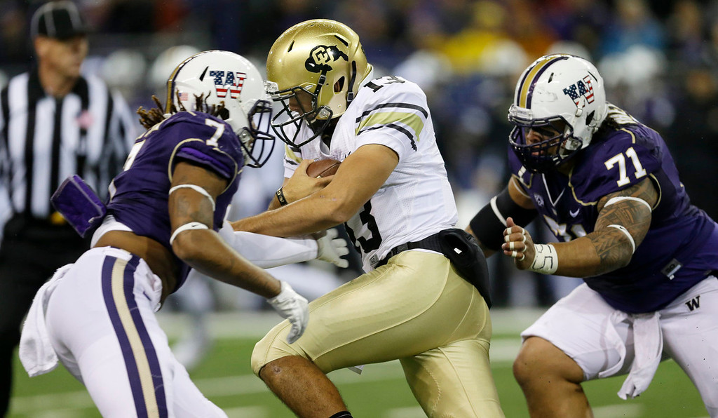 . Colorado quarterback Sefo Liufau, center, keeps the ball as he runs between Washington\'s Shaq Thompson (7) and Danny Shelton (71) just before being sacked by Shelton in the first half of an NCAA college football game on Saturday, Nov. 9, 2013, in Seattle. (AP Photo/Ted S. Warren)