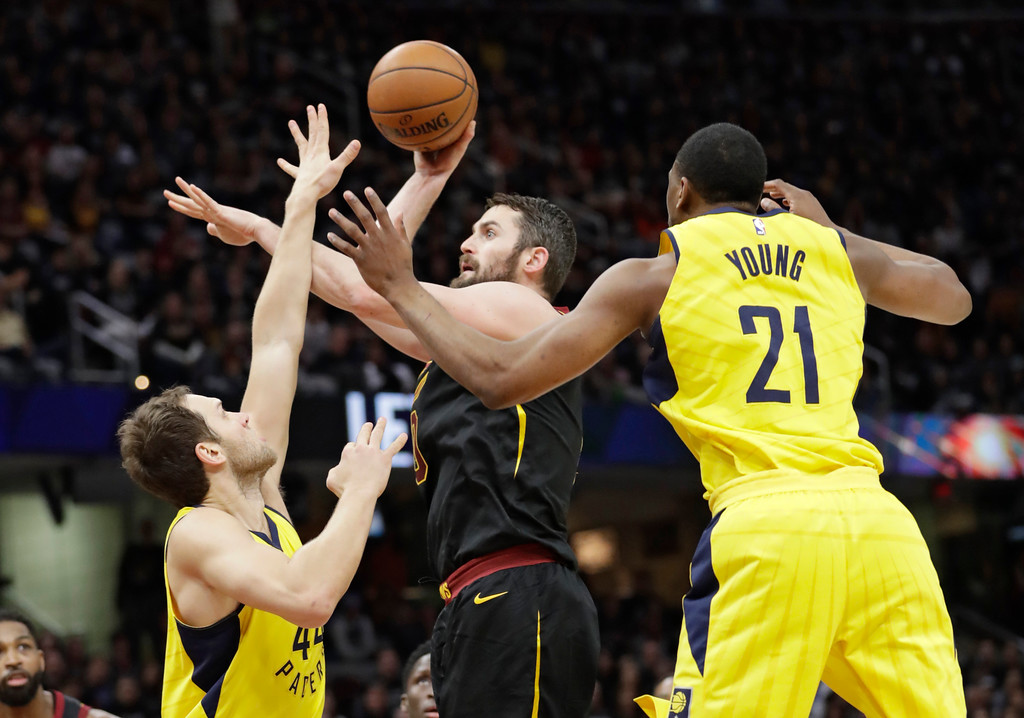 . Cleveland Cavaliers\' Kevin Love, center, shoots between Indiana Pacers\' Bojan Bogdanovic, left, from Croatia, and Thaddeus Young in the first half of Game 7 of an NBA basketball first-round playoff series, Sunday, April 29, 2018, in Cleveland. (AP Photo/Tony Dejak)
