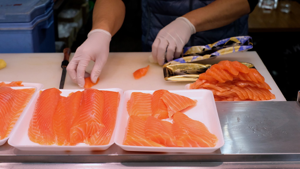 A worker preparing trays of salmon sashimi.