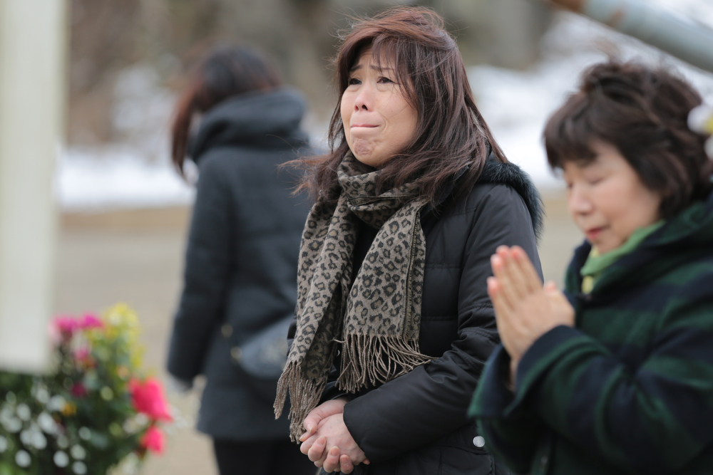. A woman reacts at Okawa Elementary School on the three year anniversary of the earthquake and tsunami on March 11, 2014 in Ishinomaki, Miyagi prefecture, Japan. On March 11 Japan commemorates the third anniversary of the magnitude 9.0 earthquake and tsunami that claimed more than 18,000 lives, and subsequent nuclear disaster at the Fukushima Daiichi Nuclear Power Plant.  (Photo by Yuriko Nakao/Getty Images)