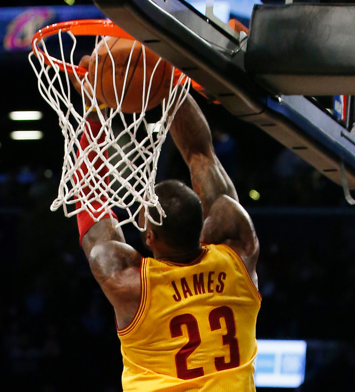 . Cleveland Cavaliers forward LeBron James (23) executes a backwards dunk in the first half of an NBA basketball game against the Brooklyn Nets, Thursday, March 24, 2016, in New York. (AP Photo/Kathy Willens)