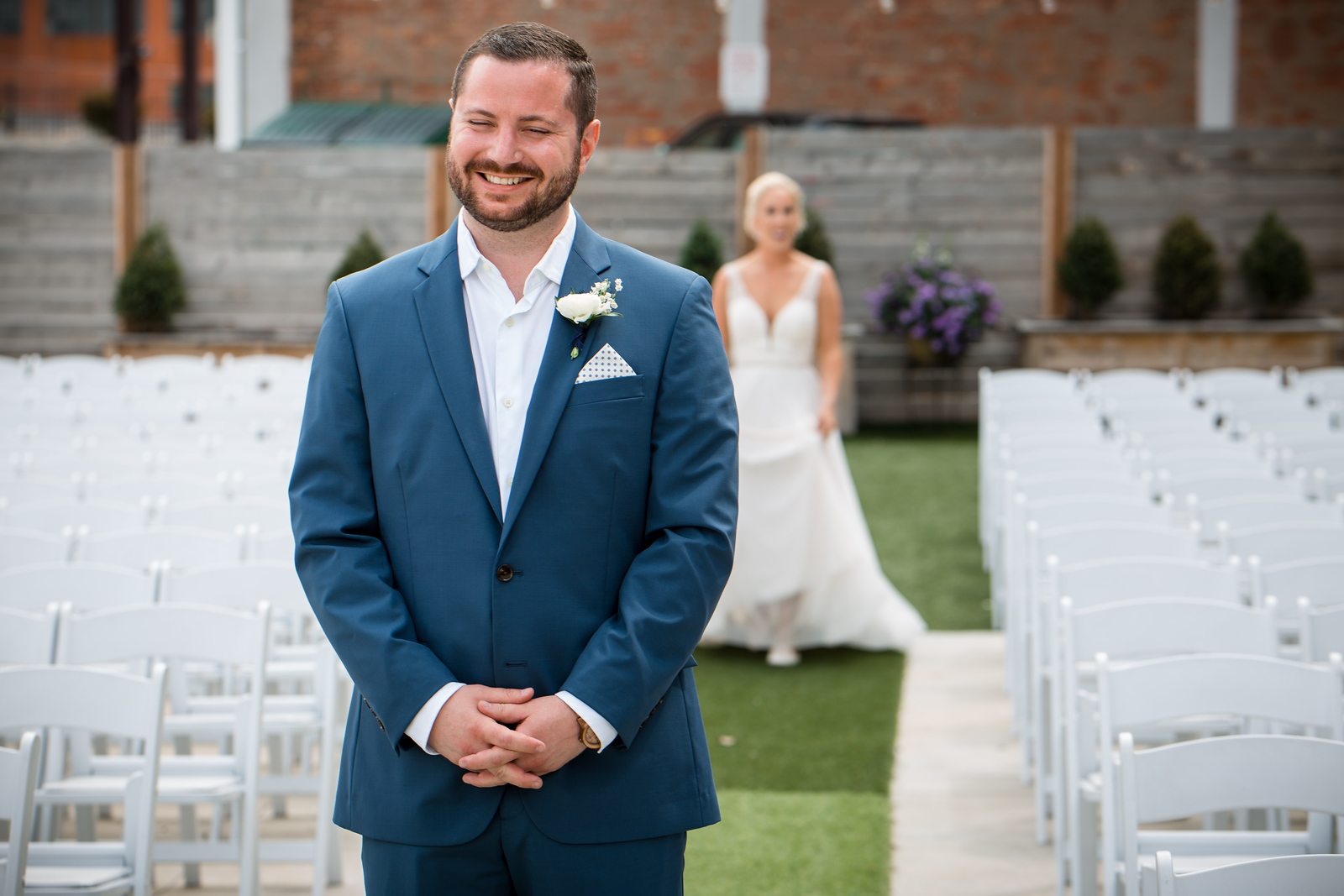 a groom standing at the altar as his bride walks up behind him for their first look