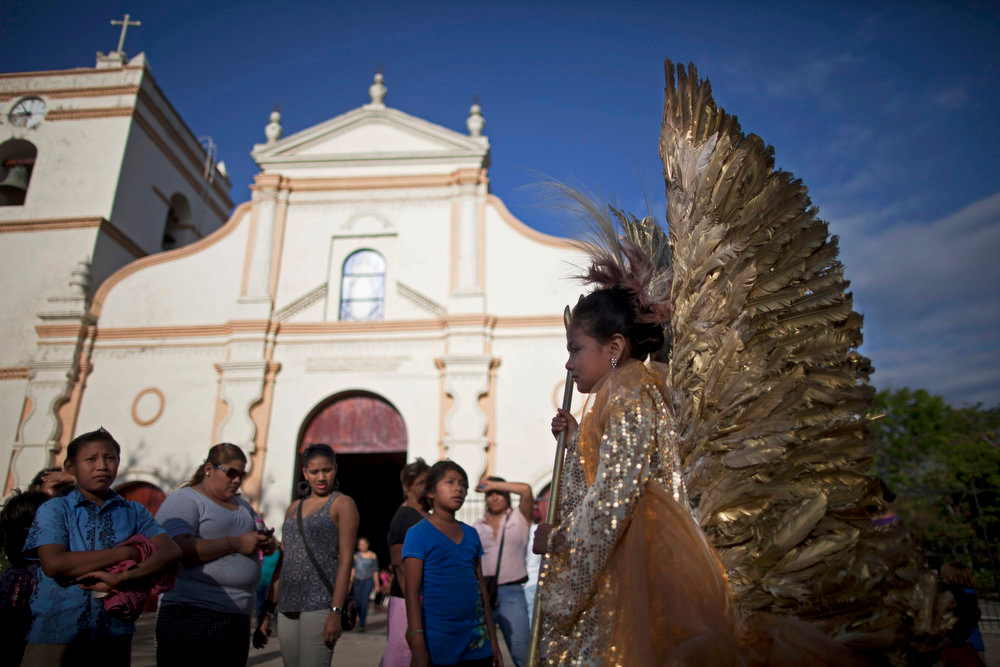 Description of . A girl wearing an angel costume wait for the start of a Good Friday procession in Masaya, Nicaragua, Friday, March 29, 2013. Holy Week commemorates the last week of the earthly life of Jesus Christ culminating in his crucifixion on Good Friday and his resurrection on Easter Sunday. (AP Photo/Esteban Felix)