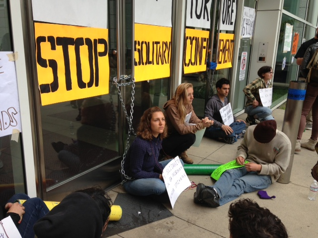 . Protesters showing solidarity with prisoners on a hunger strike are chained to the front doors of the Elihu Harris state building in Oakland, Calif., on Monday, Aug. 5, 2013. (Laura A. Oda/Bay Area News Group)