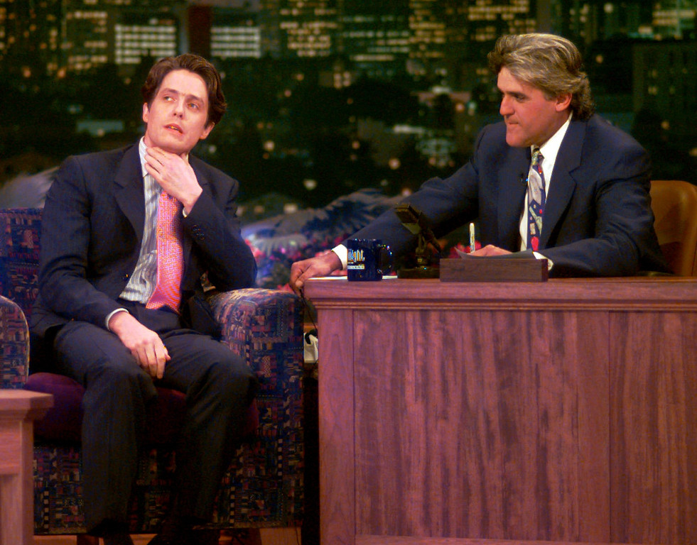 """. British actor Hugh Grant,left, reacts to a question about his arrest for lewd conduct from host Jay Leno during the early moments on \""""The Tonight Show with Jay Leno\"""" , Monday, July 10, 1995 in Burbank, Calif. It was Grant\'s first publicity appearance since his arrest involving a prostitute. (AP Photo/Eric Draper)"""