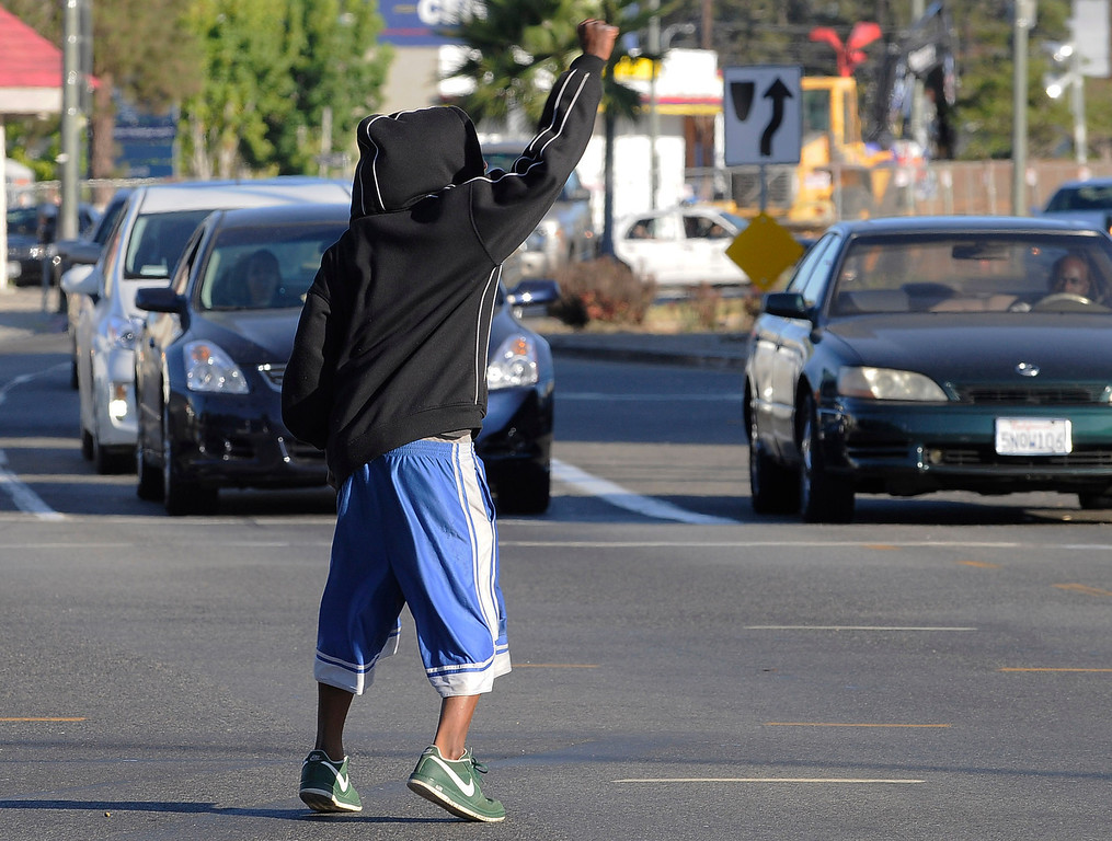 . A man in a hoodie runs out into traffic on Crenshaw Blvd. during. Crowds gather to protest while a heavy presence of Los Angeles Police Officers patrols the area around Leimert Park at the intersection of, Crenshaw Boulevard and Vernon in Los Angeles, CA. 7/16/2013(John McCoy/LA Daily News)