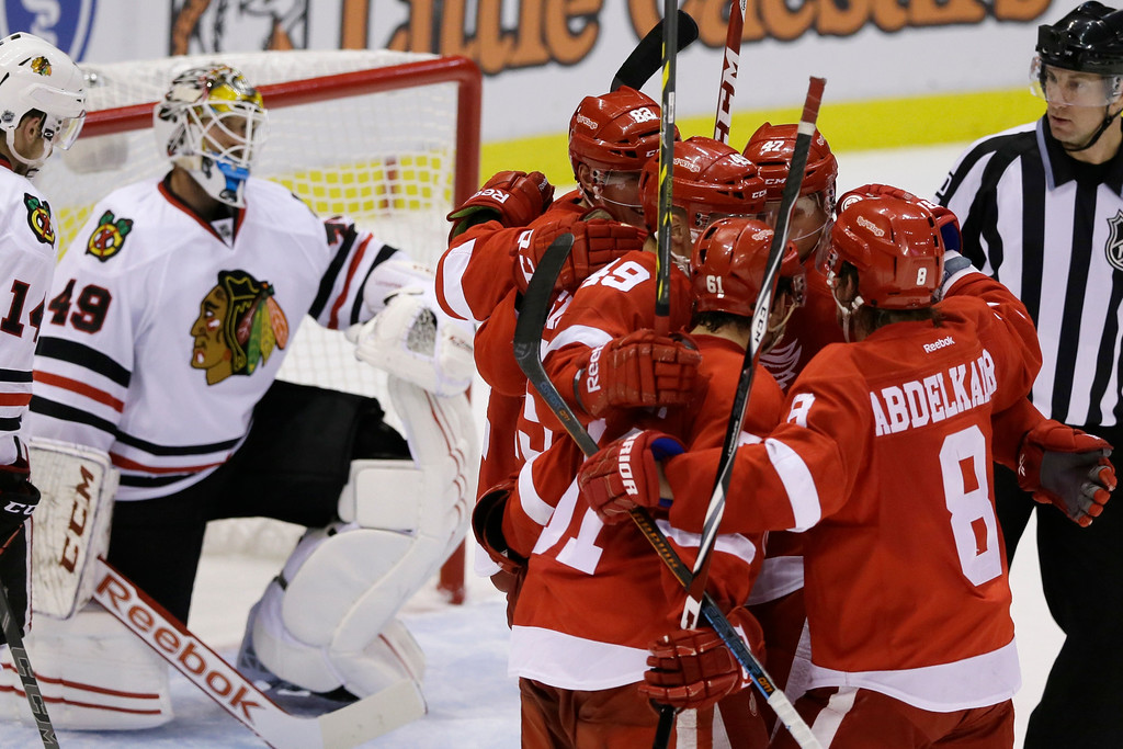 . The Detroit Red Wings celebrate in front of Chicago Blackhawks goalie Michael Leighton (49) after a goal during the third period of an NHL hockey game in Detroit, Thursday, Sept. 25, 2014. The Red Wings defeated the Blackhawks 3-2. (AP Photo/Carlos Osorio)