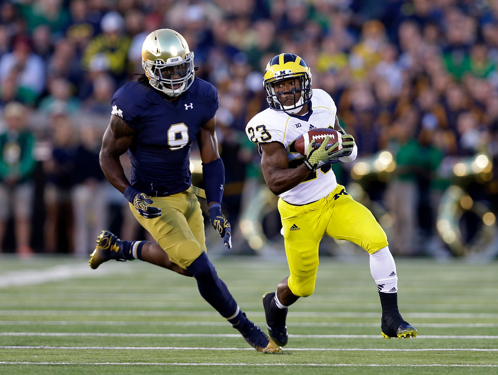 . Michigan wide receiver Dennis Norfleet runs around end after making a catch in front of Notre Dame linebacker Jaylon Smith during the first half of an NCAA college football game in South Bend, Ind., Saturday, Sept. 6, 2014. (AP Photo/Michael Conroy)
