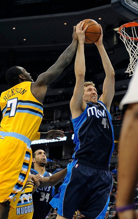 . Denver Nuggets forward J.J. Hickson battles for a rebound against Dirk Nowitzki of the Dallas Mavericks in the first quarter Wednesday night at the Pepsi Center. (Photo By Steve Nehf / The Denver Post)