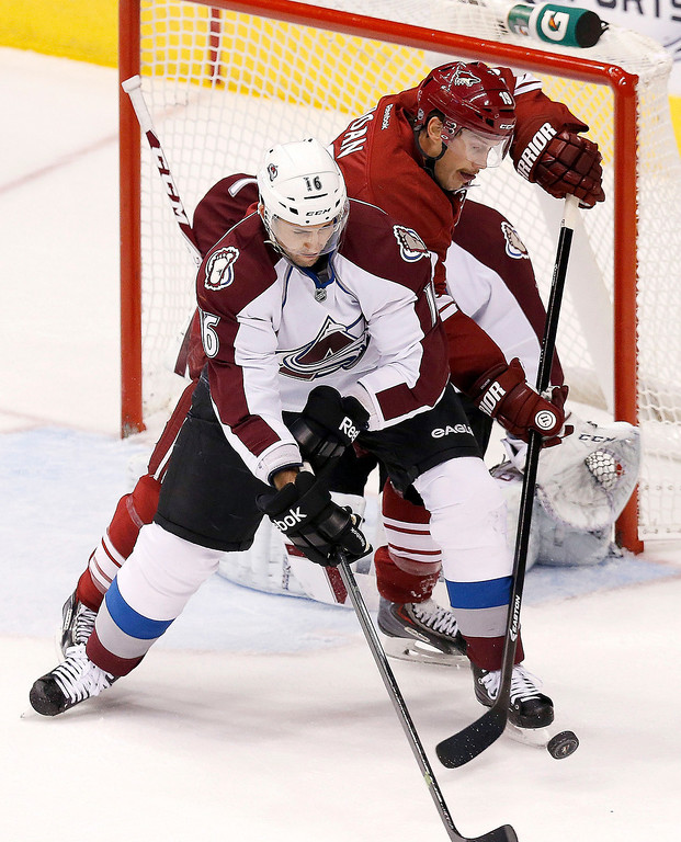 . Colorado Avalanche\'s Cory Sarich, front, and Phoenix Coyotes\' Shane Doan battle for the puck during the first period of an NHL hockey game Thursday, Nov. 21, 2013, in Glendale, Ariz. (AP Photo/Ross D. Franklin)