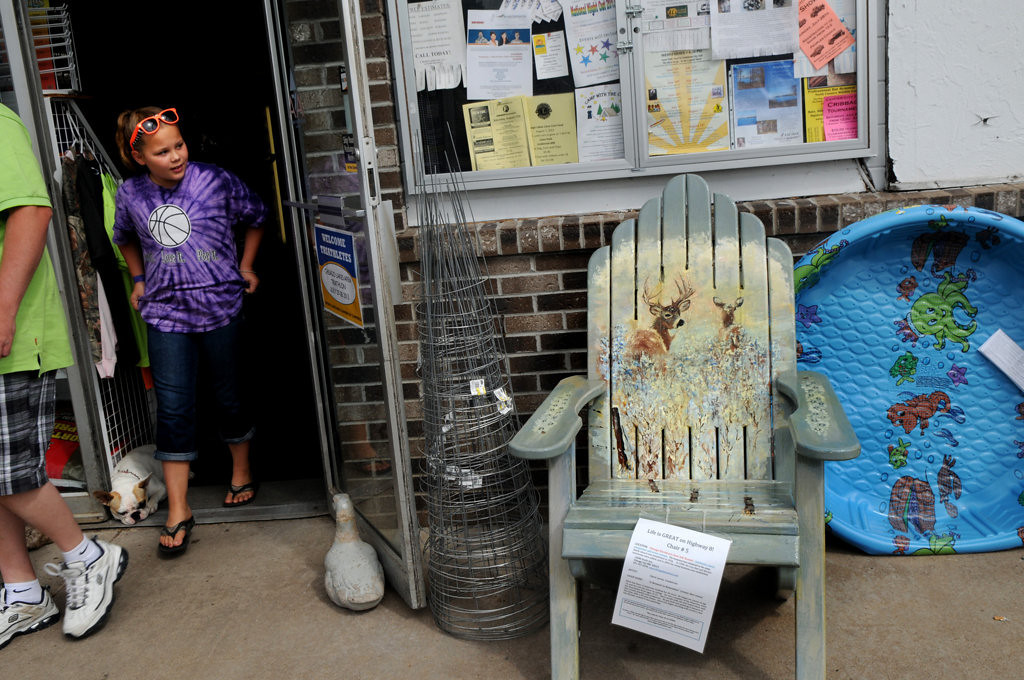 ". Jenna Whitmore, 11, River Falls, walks out of a Chisago True Hardware store Friday July 26, 2013. The chair by the store is titled ""A Moment to Remember\"" by Steve Levey and is part of the Highway 8 Chairs project in Chisago County. (Pioneer Press: Jean Pieri)"