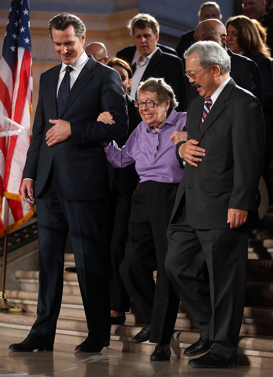 . Former San Francisco mayor Gavin Newsom, left, and current Mayor Edwin Lee, right, escort longtime gay rights activist Phyllis Lyon, center, to her seat as they celebrate at City Hall in San Francisco, Calif., on Wednesday, June 26, 2013. The U.S. Supreme Court dismissed California\'s Proposition 8 and declared the 1996 Defense of Marriage Act unconstitutional. (Jane Tyska/Bay Area News Group)
