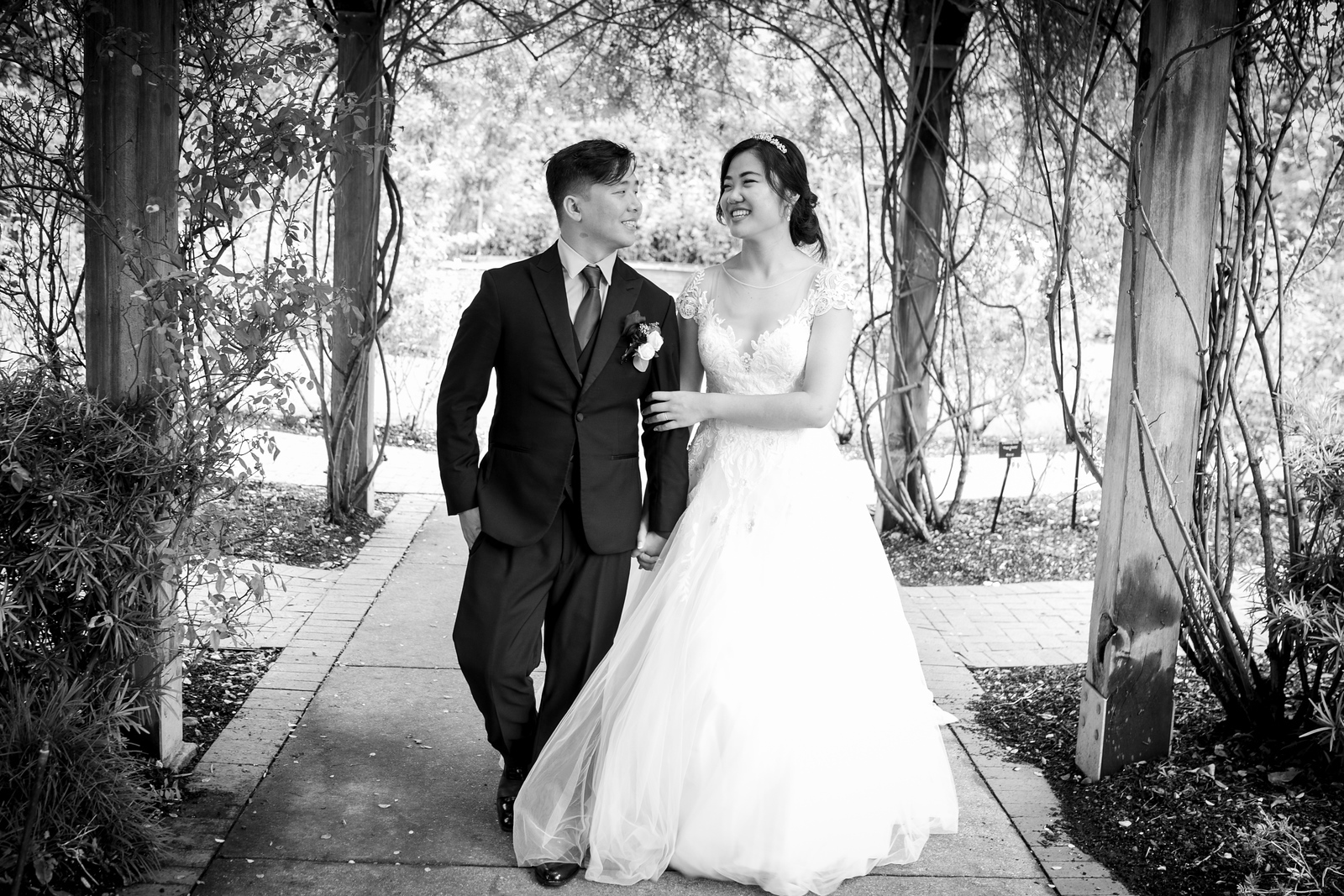 A bride and groom walking down through vined gardens locking arms and smiling at one another