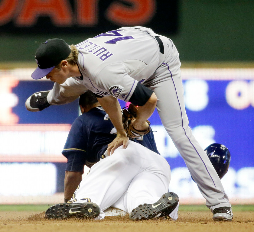 . Milwaukee Brewers\' Carlos Gomez gets tangled with Colorado Rockies\' Josh Rutledge (14) as he is caught stealing second during the eighth inning of a baseball game Friday, June 27, 2014, in Milwaukee. (AP Photo/Morry Gash)